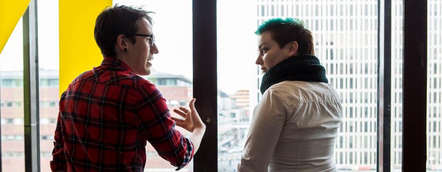 Par sitter vid fönster och diskuterar