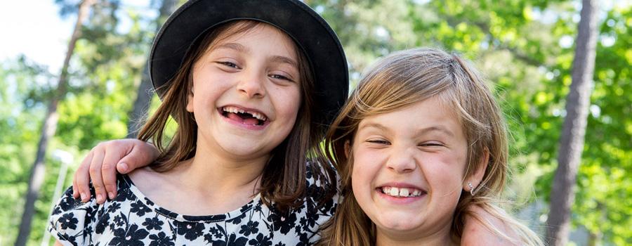 Två glada kompisar på skolgården