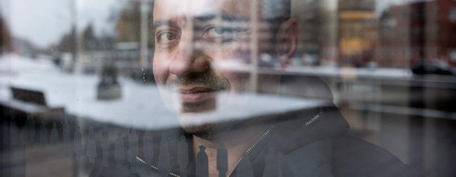 En man sitter invid ett fönster och tittar ut genom fönstret och in i kameran.