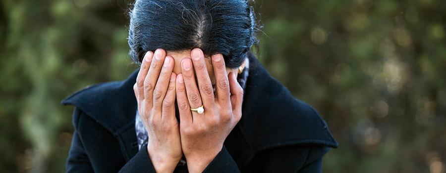 Kvinna med grönska bakom sig lutar sig framåt och håller händerna för ansiktet.