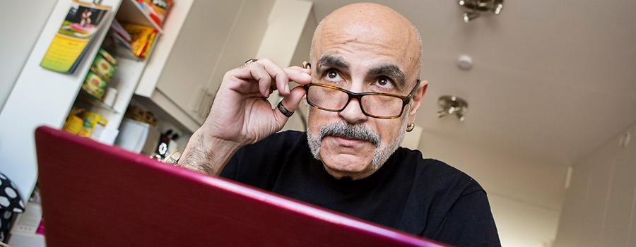 En man med glasögon sitter vid en dator och blickar upp.