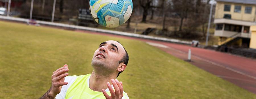 En träningsklädd man står på en fotbollsplan och nickar en boll.