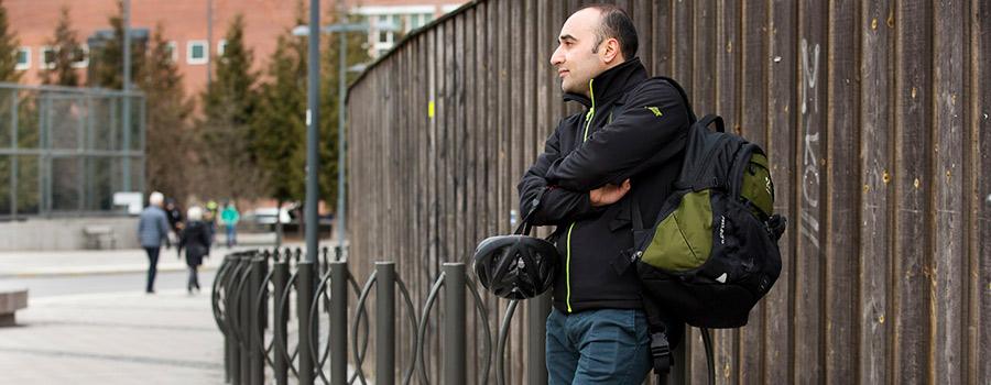 En man med cykelhjälm och ryggsäck står vid ett cykelställ och har armarna i kors.