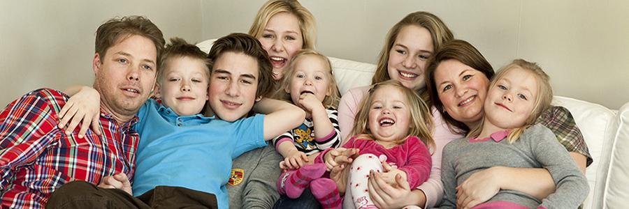 En familj på nio personer sitter i en vit soffa och ser glada ut.